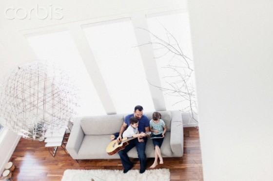 Father with children (6-7, 2-3) playing guitar at home