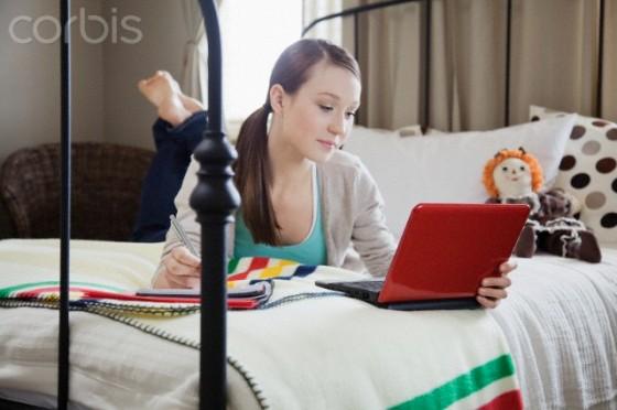 Teen using laptop in bed